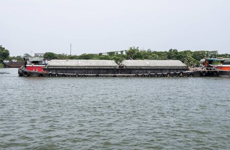 The large cargo boat is loading the sand for transport to the construction site in the large river,Bangkok Thailand.
