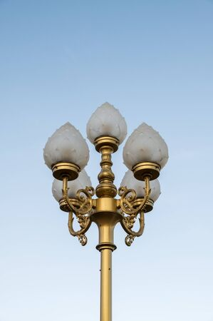 Electrical lamp with the traditional Thai pattern on the golden pole in the Thai temple.