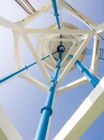 View from the bottom of the white water tower which under the clear blue sky in the urban area.