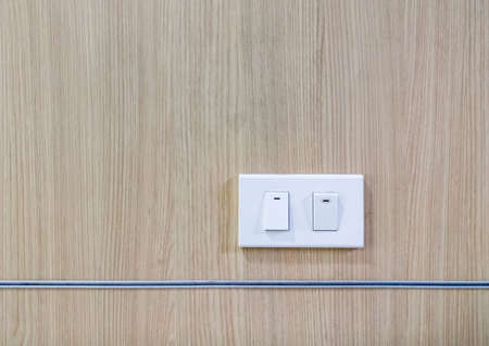 Modern light switch (plastic frame) is turned on and turned off on the veneer wall of the meeting room in the home office.
