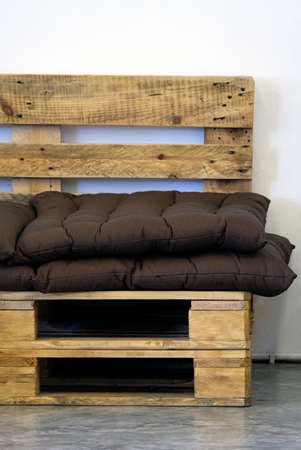Handmade chair from the wooden pallet with the soft pad near the loft wall in the coffee cafe.