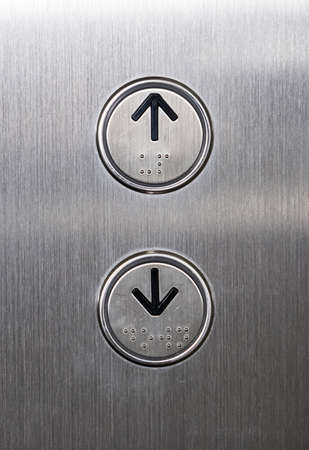Arrow symbol with the braille on the push button of the metal panel in the passenger elevator,office building in the urban area.