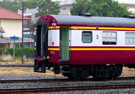 The rear of the bogie third class carriage of the ordinary train in the yard of the urban station, rain time before leaving from the station.