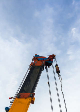 Closeup of the high crane with many slings for lifting the construction equipment in the construction site for built the office building in the city.