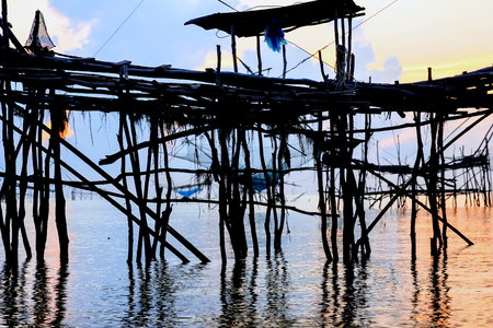 In the morning at Pak Pra lake,Pattalung,Thailand. Silhouette of traditional fishing method using a bamboo square dip net