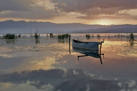 Fishing boat in lake at rising sun photo