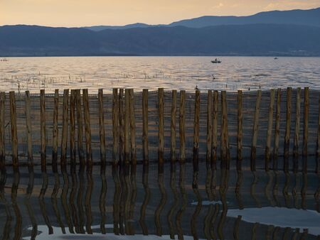 peacefulness: Reflection of the wooden fence in lake at sunset