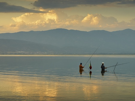 Two fishermen in the lake on sunset   photo