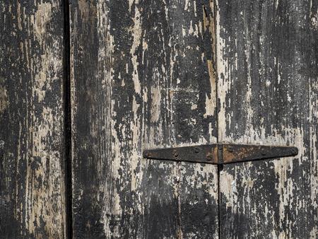 hinge: old rusty hinge on black wooden door