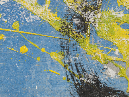canvas background: brush strokes amd grunge of blue, yellow, and black acrylic paint on a dusty old metal fence, close up of abstract  textured background
