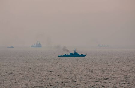 Military navy ship with smoke coming out of pipe sailing in the sea with cargo ships silhouettes at the horizon
