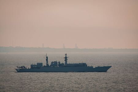 Military ship naval forces sailing in the Black sea with buildings and a plant on the background. Military training. Gloomy foggy morning Stok Fotoğraf
