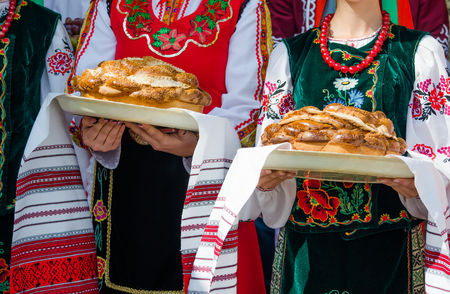 Girls in ethnic Bulgarian clothes holding traditional beautiful loaf as a greeting on a towel with pattern. Concept of slavic hospitality. Celebration. Banco de Imagens