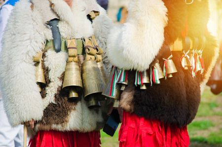 Costumed Bulgarian men Kuker who perform traditional rituals. White furry jackets with bells and ribbons with colors of Bulgaria. Warm sunlight effect. Ethnic celebration 免版税图像