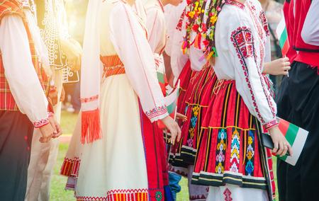 Unerkennbare Irls in ethnischen bulgarischen Kostümen mit bunten Ornamenten. Sonnenuntergang im Hintergrund