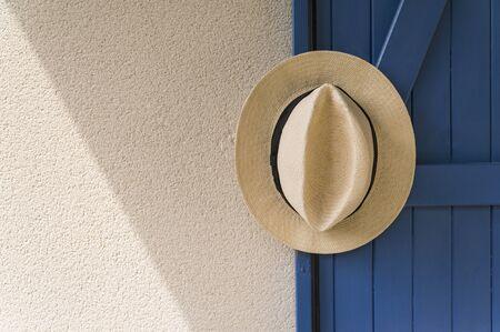 headwear: Panama hat hanging from blue wooden door
