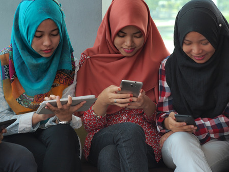 Three students engrossed with electronic gadget