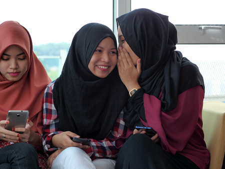 outcast: A girl is whispering to a friend while another is being neglected Stock Photo