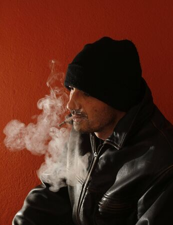 puffing: thoughtful man smokes joint, dependence and cigarettes