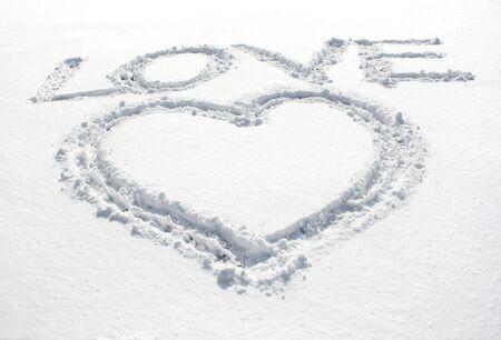 heart and inscription love written on glittering snow photo