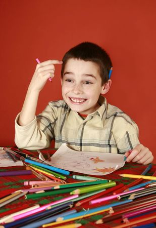 ingenious: freckled boy musing and drawing, hit upon, come to mind Stock Photo