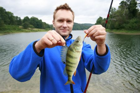 predilection: Happy fisherman presents perch, caught big fish  Stock Photo