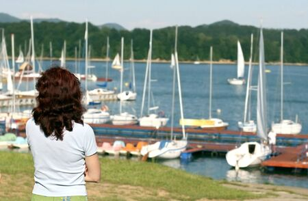 alienation: woman standing alone on marina, longing girl in solitude, secret fatal girl