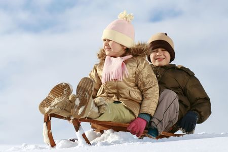 sister and brother on sledge, winter friendship photo