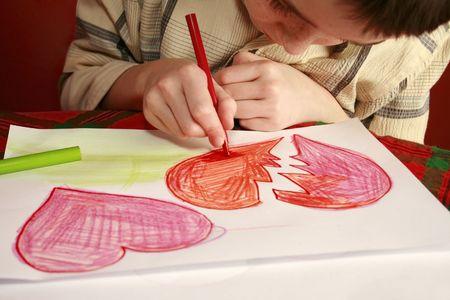 boy drawing valentine hearts, hurt my feelings