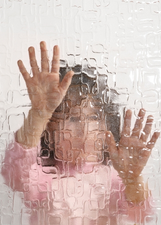 undistinguishable young girl behind pane, depression Stock Photo