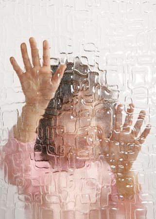 undistinguishable young girl behind pane, depression Stock Photo