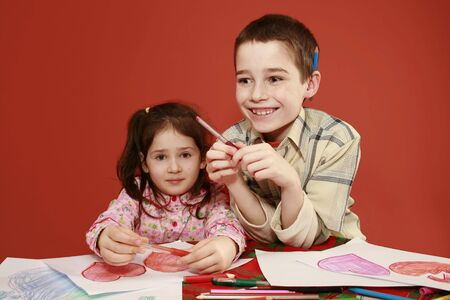 imaginativeness: sister and brother togetherness, children collectively drawing valentine hearts