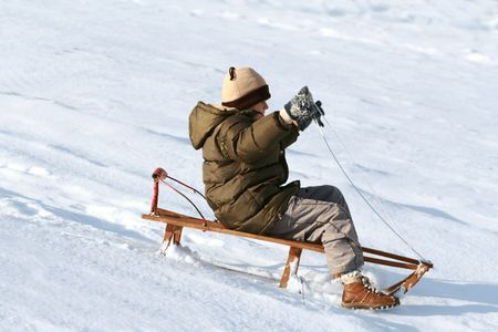 young boy on sledge, winter and fun photo