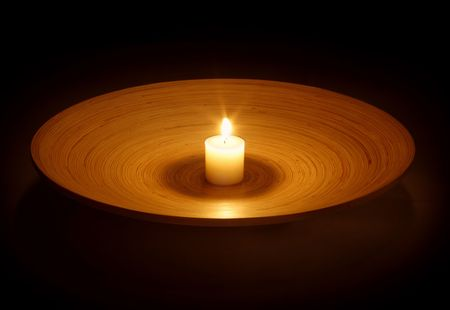 clearness: burning candle on wooden platter