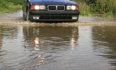impediment: water splashes from under the wheels, dangerous ride of the car through large water, flood, reckless driving, driving through a river overflow, water on road after downpour, obstacle course, come encounter an obstacle Stock Photo