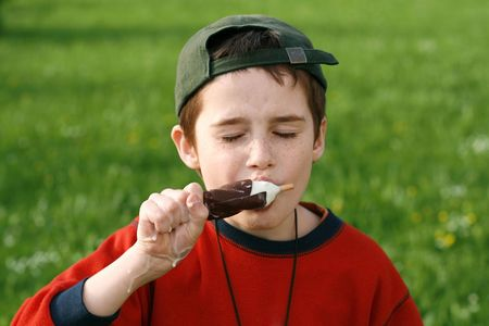 boy eating ice cream on a stick, wolf down Stock Photo