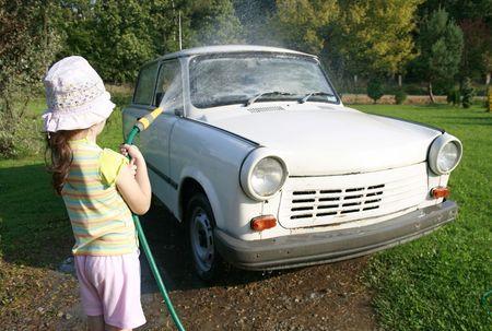 auto lavado: ni�a pulverizaci�n un coche con una manguera de agua en una tarde soleada, tubo de goma, vierta agua en m�s de Foto de archivo