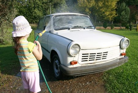 oldschool: young girl spraying a car with a water hose in a sunny afternoon, rubber hose, pour water on over Stock Photo