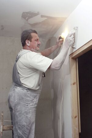 Man plastering wall with work tools photo