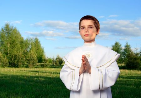 Boy portrait in his first holy communion, praying hands, clear conscience Stock Photo