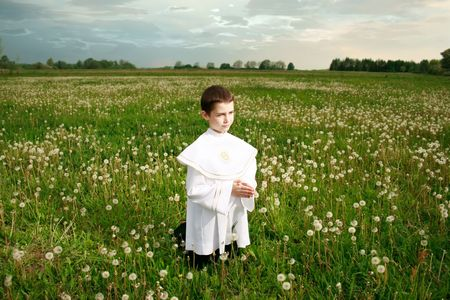 boy child portrait in his first holy communion, praying hands, clear conscience  photo