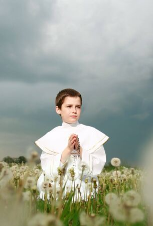 child in his first holy communion, praying hands, purity soul Stock Photo