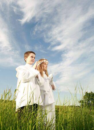 vormsel: jongen en meisje in eerste communie, zuiver geweten, bidden voor handen  Stockfoto