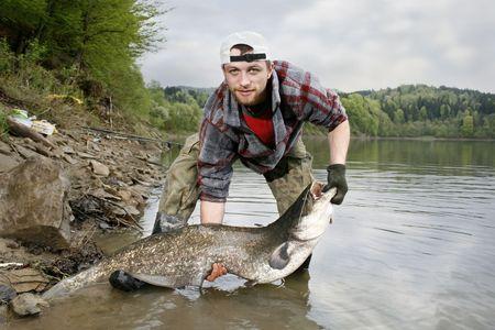 sheatfish: Un pescador feliz presentando su trofeo de pesca atrapados en un lago polaco - bagre (Silurus glanis)