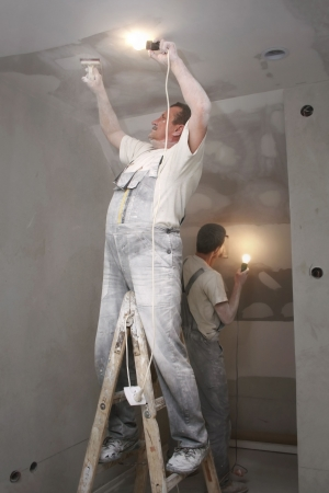 plastering: Man plastering wall with work tools