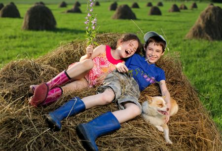 Summer lanscape with hay cocks, couple children sitting on large hay