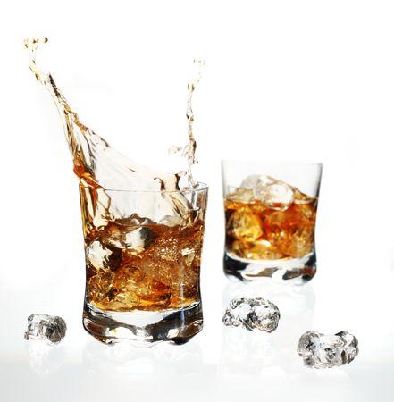 Splashing, dynamic splash of whisky with ice cube on white background