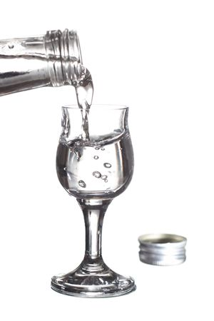 distillate: pouring vodka from a bottle into a glass Stock Photo
