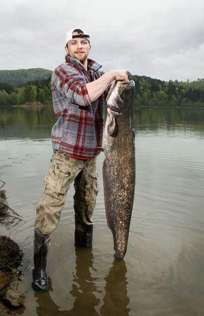 p�cheur: Un p�cheur heureux pr�sentant son troph�e de la p�che captur�s dans un lac polonais - poisson-chat (Silurus glanis)