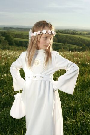 girl in first holy communion on landscape photo